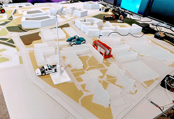 Mock-up of streets with police car, red bus & cables