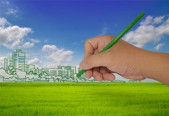 Hand drawing a green smart city with green pencil on grass