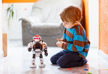 Little boy playing with remote control robot on the floor
