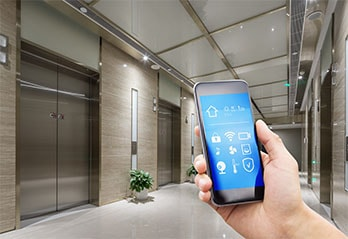Person holding a smart phone with icons in front of a lift in a hallway